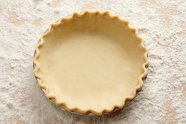 Empty Pie Crust An empty pie crust on a table laden with flour. pastry dough stock pictures, royalty-free photos & images