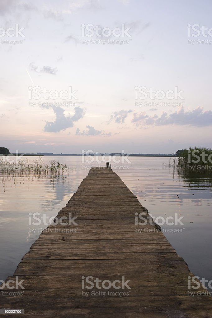 empty pier by lake at dawn stock photo