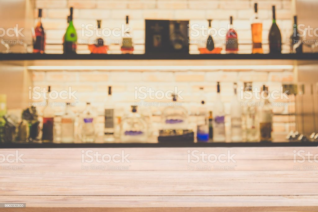 Empty pine wooden bar counter with blur background bottles of...