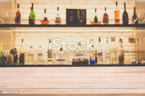 1013514594 istock photo Empty pine wooden bar counter with blur background bottles of restaurant. 990232300
