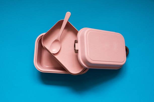 leere rosa bento-lunchbox mit löffel auf blauem hintergrund - besteck günstig stock-fotos und bilder