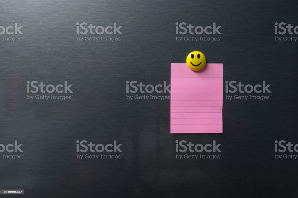 Empty pink paper on refrigerator door with smilling face on magnet. stock photo