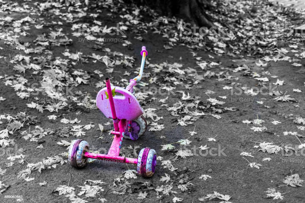 Empty pink tricycle in autumn leaves at playground stock photo