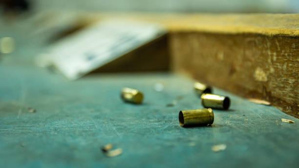 leere pistolenkugeln auf holztisch in einem schießstand - tatort von menschen geschaffener raum stock-fotos und bilder