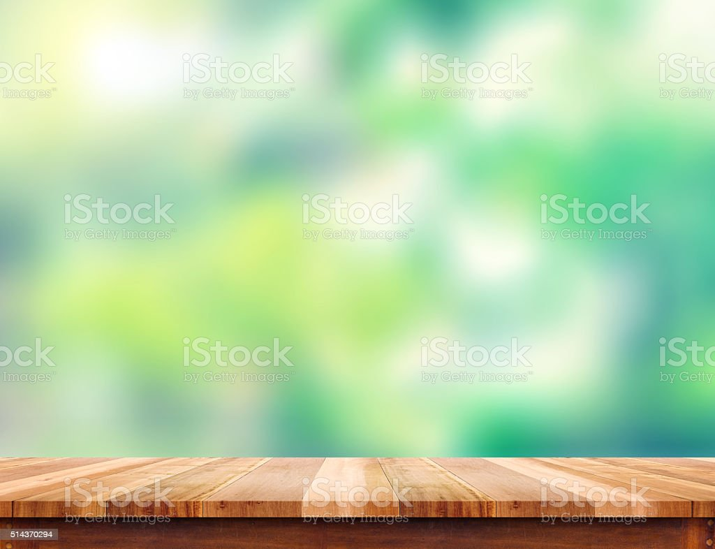 Empty plank brown wood table top with blur green tree stock photo