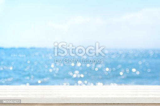 istock Empty plank white wood table top with blur blue sky and sea boekh background,summer holiday backdrop.Mock up template for display or montage of product or content use as panoramic banner in ads. 963562622