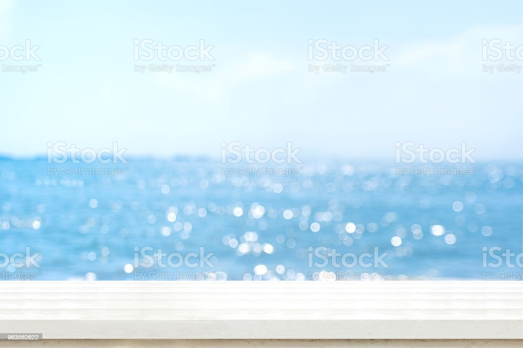 Empty plank white wood table top with blur blue sky and sea boekh background,summer holiday backdrop.Mock up template for display or montage of product or content use as panoramic banner in ads. stock photo