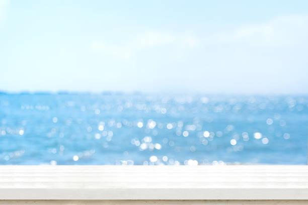 lege plank wit houten tafelblad met vervagen blauwe hemel en zee boekh achtergrond, zomer vakantie achtergrond. mock up sjabloon voor montage van het product of het gebruik van de inhoud als panoramisch banner in advertenties of weergeven. - summer background stockfoto's en -beelden