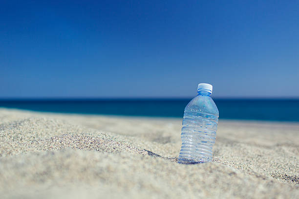 empty plastic bottle on the sand beach - ocean plastic stock pictures, royalty-free photos & images
