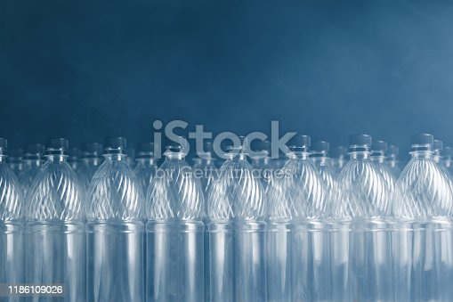 empty plastic bottles on black background with smoke, pollution concept