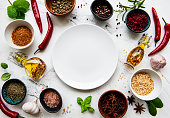 Empty  plate and frame of spices, herbs and vegetables on a white marble background. Top view, flat lay.