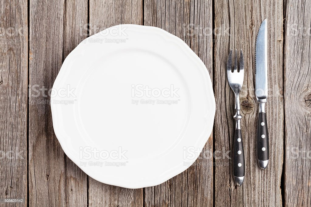 Empty plate and silverware on wooden table stock photo