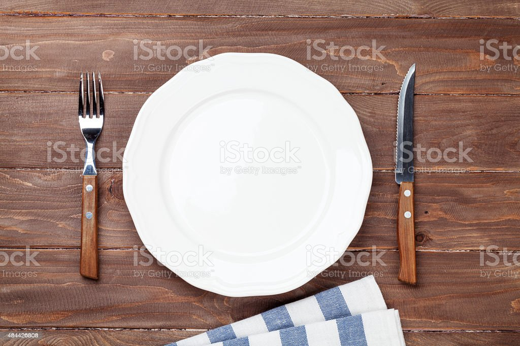 Empty plate and silverware over wooden table stock photo