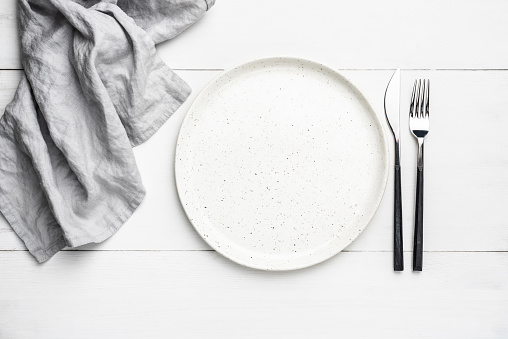 Empty plate, cutlery and linen textile