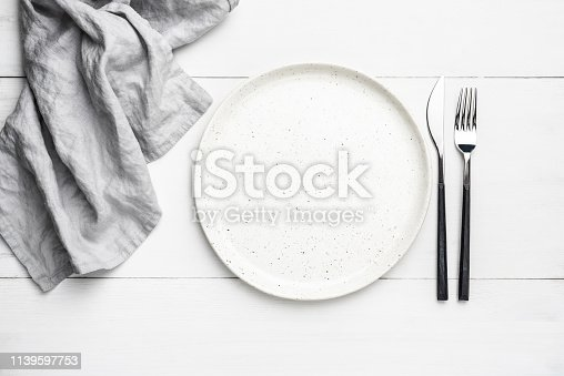 Empty plate, cutlery and linen textile. Table setting with copy space for text