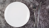 Empty plate, fork and knife on the dark background.