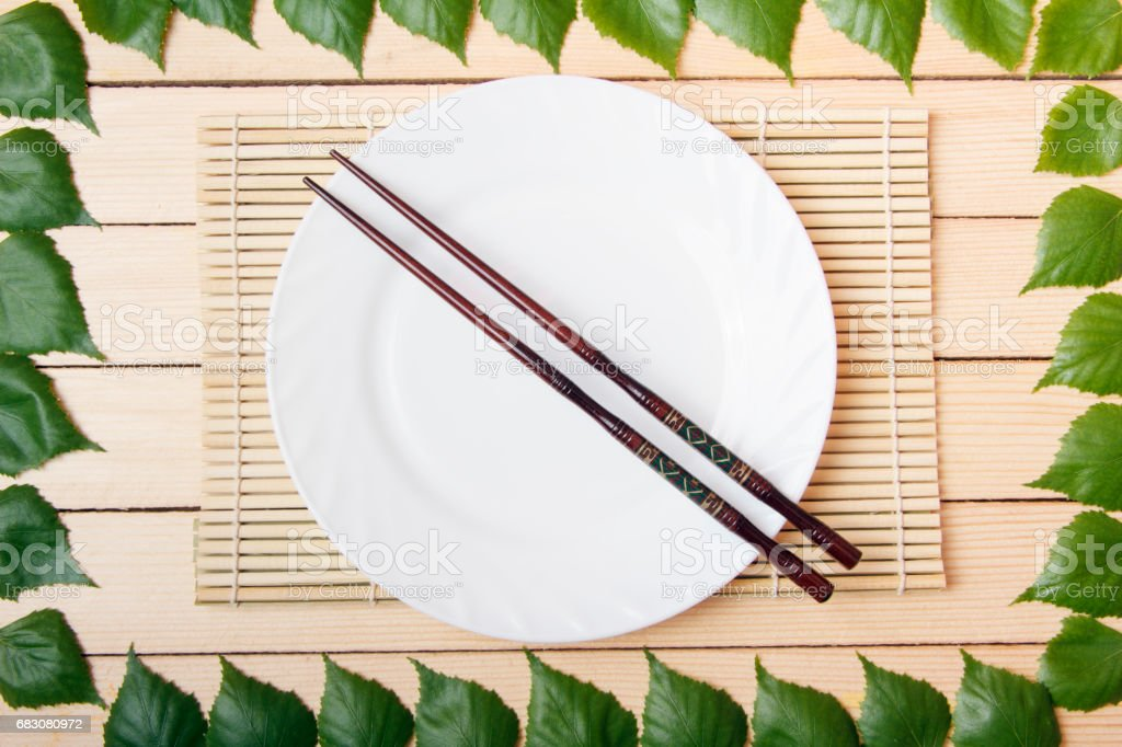 Empty plate on a bamboo mat with chopsticks, top view, on a wooden background, framed with leaves of a tree foto de stock royalty-free
