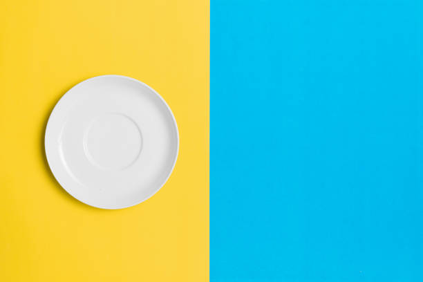 Empty plate on a contrasting yellow and blue background. stock photo