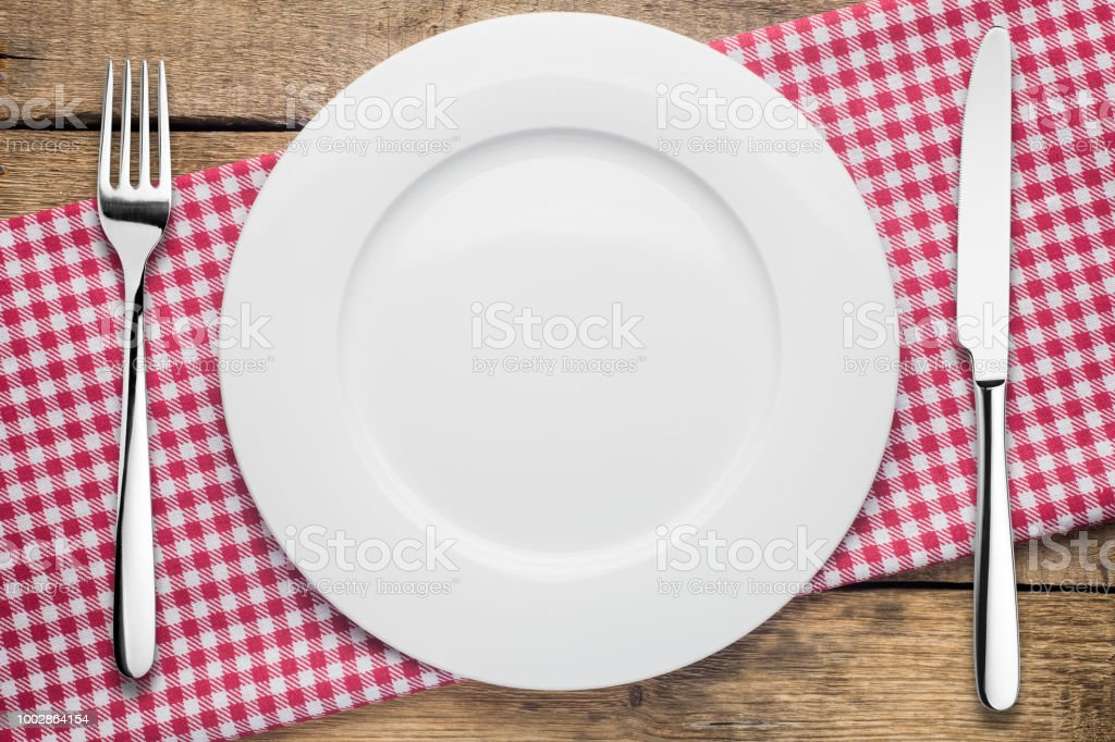 leeren Teller auf einem hölzernen Hintergrund, eine Serviette in ein rot-weißes - Lizenzfrei Alt Stock-Foto