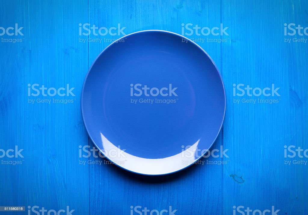 Empty plate on blue table stock photo