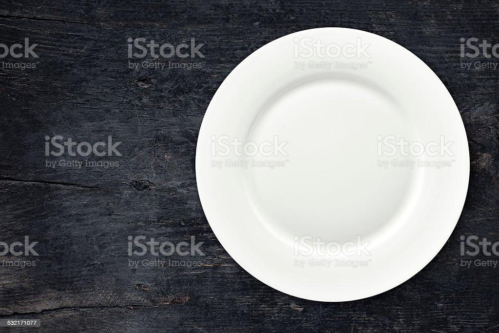 Empty plate on dark wooden table stock photo