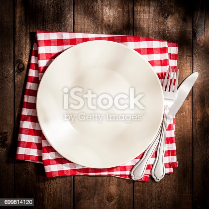 Top view of an empty plate on a red and white checkered textile napkin ready for menu text or any food with a fork and knife beside it shot on rustic wooden table. Predominant colors are brown and red. Low key DSRL studio photo taken with Canon EOS 5D Mk II and Canon EF 100mm f/2.8L Macro IS USM