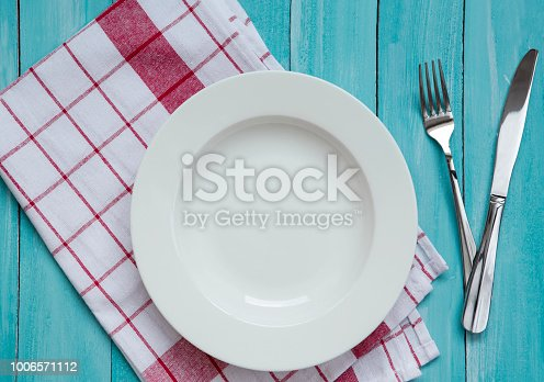 Empty plate, red checkered napkin, fork and knife on wood