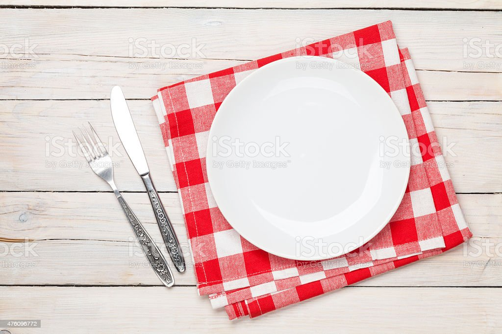 Empty plate, silverware and towel over wooden table background stock photo