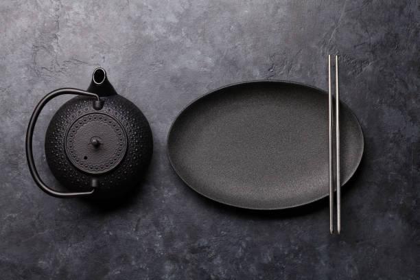 leere platte, teekanne und stäbchen - keramikteekannen stock-fotos und bilder