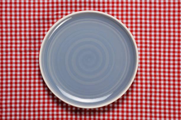 leeren teller mit karierten tischdecke - roten küchentische stock-fotos und bilder