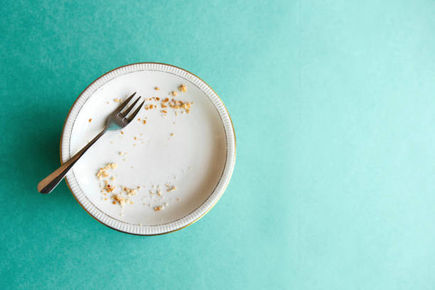 empty plate with crumbs after eating on a green background. the concept of the end of the holiday or celebration. nearby place for text - briciola foto e immagini stock