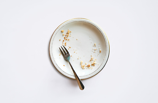 Empty plate with crumbs after eating on a white background.