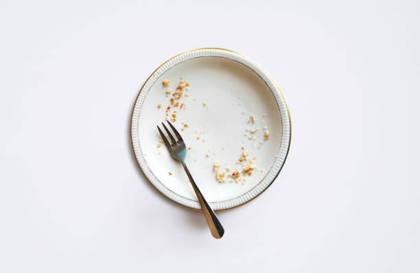Leere Platte mit Krümel nach dem Essen auf weißem Hintergrund. – Foto