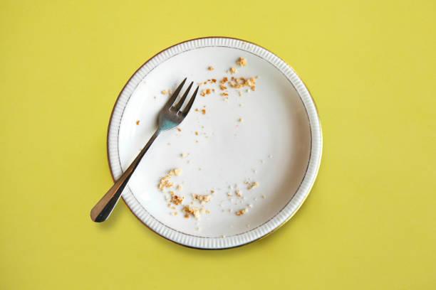 töm plattan med smulor efter att ha ätit på gul bakgrund. begreppet i slutet av semestern eller firandet - tallrik uppätet bildbanksfoton och bilder