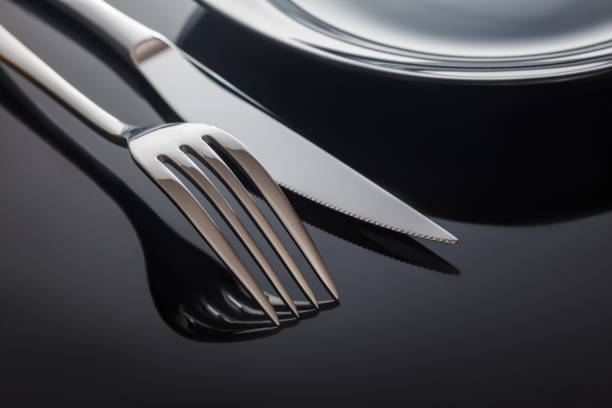Empty plate with knife and fork on a black background stock photo