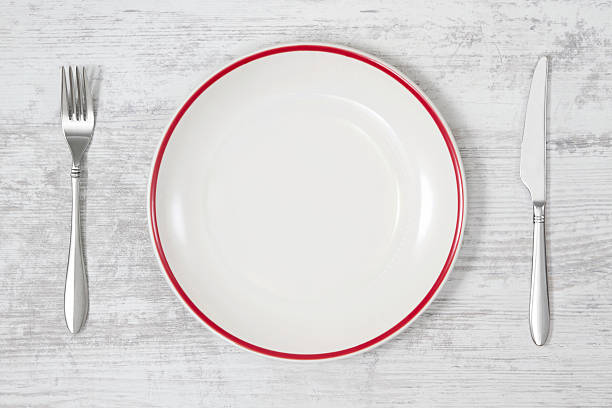 Empty Plate with Knife and Fork on White Kitchen Table stock photo