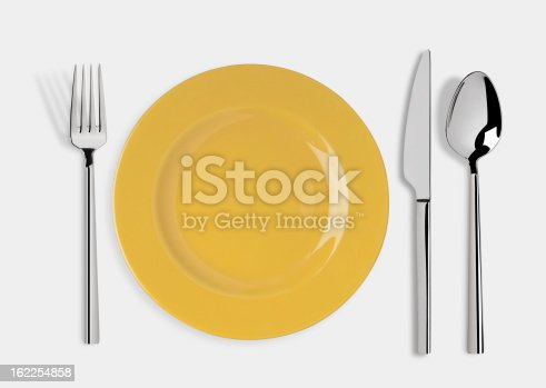 Empty yellow plate and fork,spoon and table knife isolated on white background. Include clipping path.