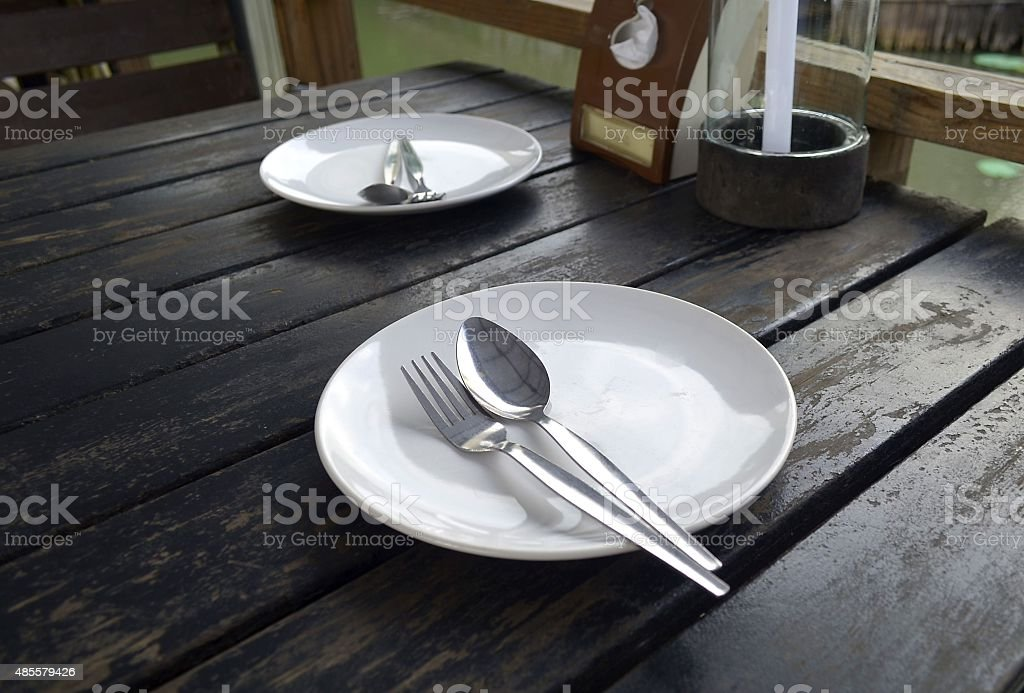 Empty plate with spoon and fork on wooden table stock photo