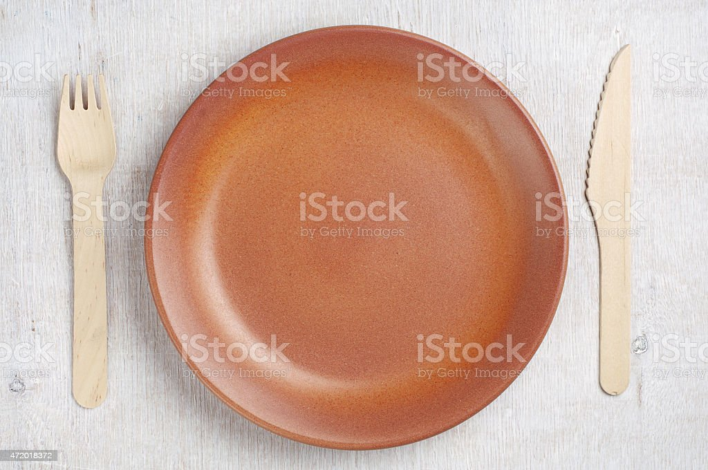 Empty plate, wooden fork and knife stock photo
