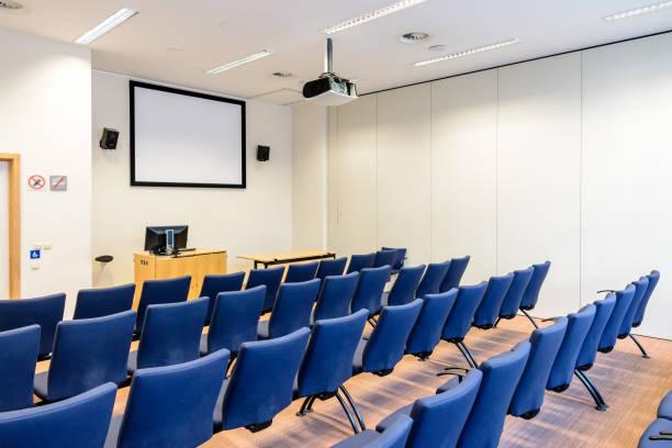 Salle de présentation vide avec rangées de sièges, écran de projection et vidéoprojecteur au plafond. - Photo