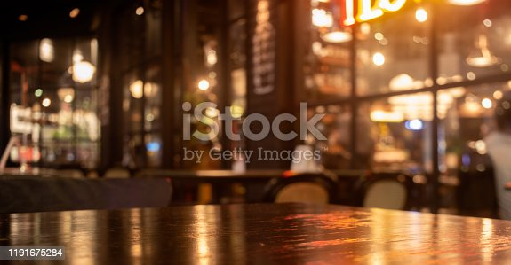 istock Empty real wood table top with light reflection on scene at restaurant, pub or bar at night. 1191675284