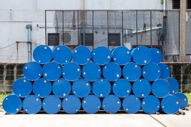 leere recycelbare chemische tanks aus blauem stahl für ölbrennstofffässer, die in einer reihe im werkslager gestapelt sind. hintergrund und textur - opec stock-fotos und bilder