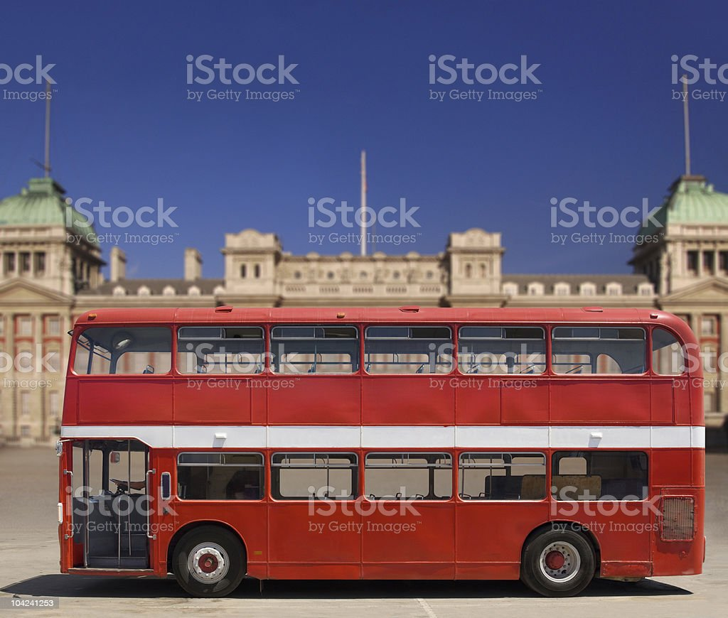 A empty red double decker bus in front of a building stock photo