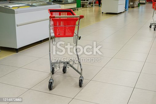 istock Empty red grocery basket with cart in supermarket aisle 1214572883