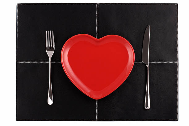 empty red heart plates with  knife fork on black leather stock photo