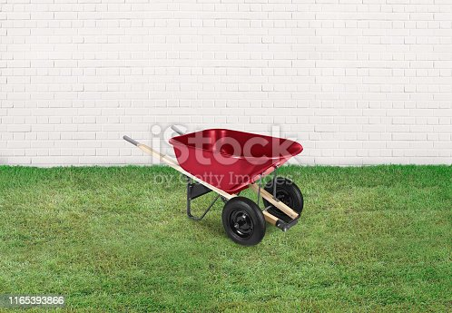 Empty red wheelbarrow in front of a white brick wall with grass