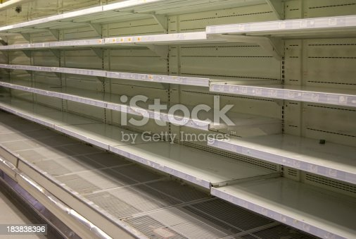 A row of empty refrigerated shelves in a supermarket that is going out of business.