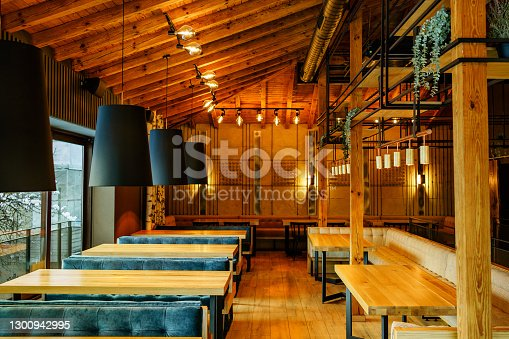 Interior of wooden retro restaurant with empty chairs, tables and other furniture, without people