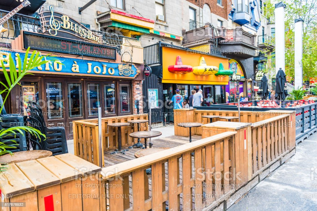 Empty restaurants outside seating area with tables on Saint Denis street in Montreal's Plateau Mont Royal in Quebec region stock photo