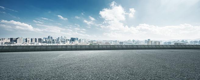 empty asphalt road with cityscape of hangzhou in cloud sky
